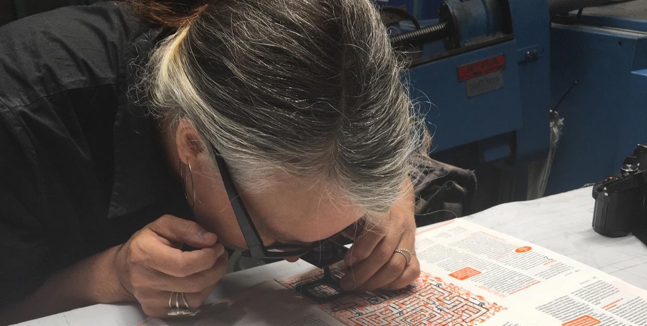 """Grafiker Helle Vibeke Jensen nærstuderer de første trykprøver af """"Bibelen til konfirmander"""". Foto: Bibelselskabet."""