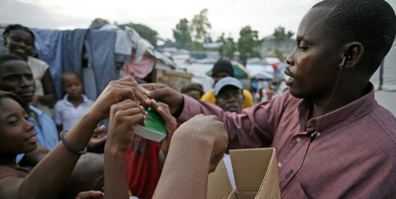 Bibelselskaber over hele verden gør Bibelen tilgængelig gennem nye oversættelser og uddeling af bibler. Her uddeler det haitianske bibelselskab Det Nye Testamente på kreolsk i en flygtningelejr på Haiti. Foto: United Bible Societies.