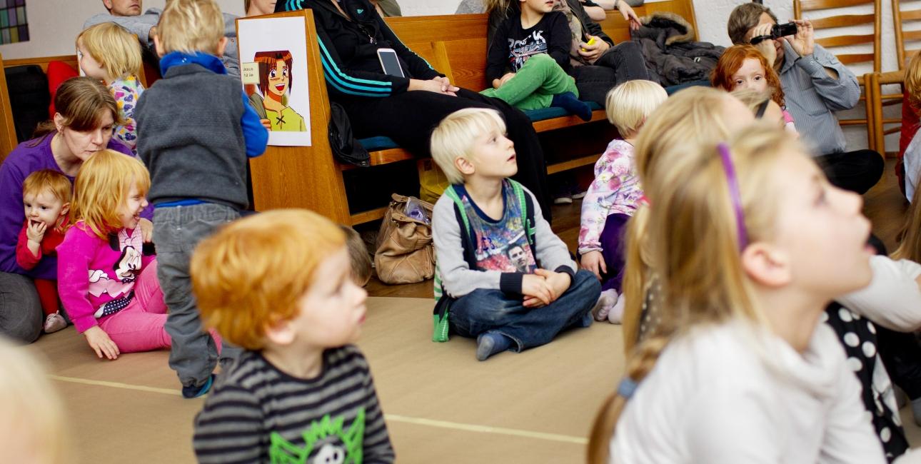 Børnene lytter til præsten.