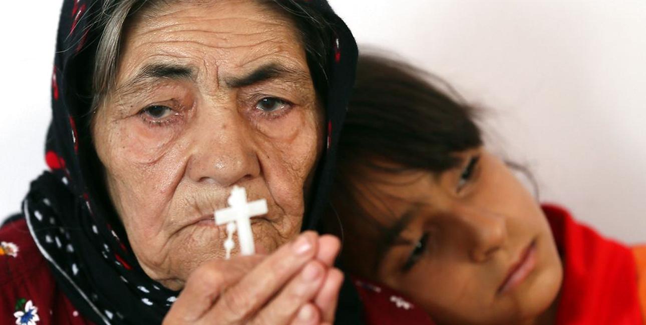 En irakisk kvinde beder sammen med sit barnebarn. Irak er et af de lande, hvor mange kristne har måttet flygte fra voldelige islamistiske ekstremister. Foto: Karim Sahib/Scanpix