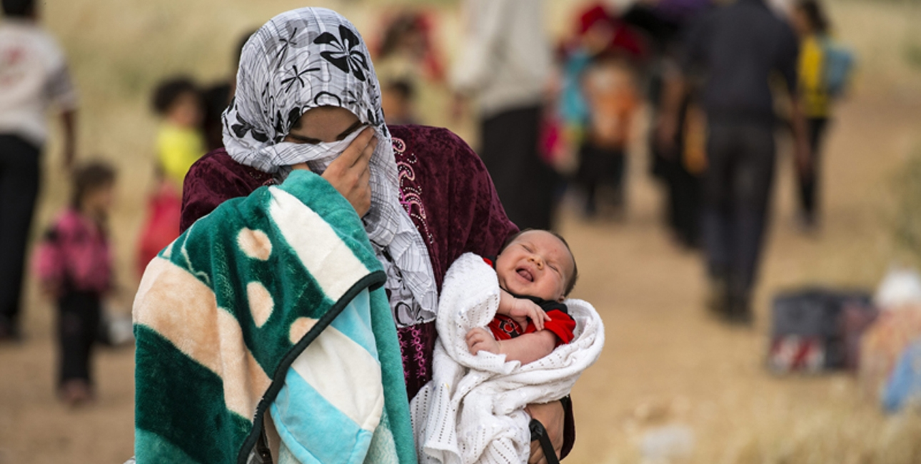 Mor er på flugt fra Syrien med sit barn på armen. Foto: UBS.