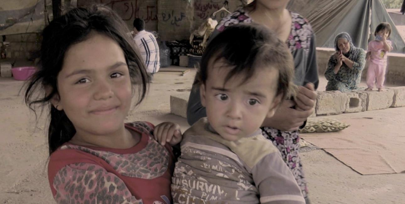 Pigen her er flygtet fra Irak sammen med sin familie. I en måned har hun sammen med sin søster sovet på den kolde jord, men nu smiler hun, fordi hun har fået en madras af Bibelselskabet. Foto: Andrea Rhodes, De Forenede Bibelselskaber