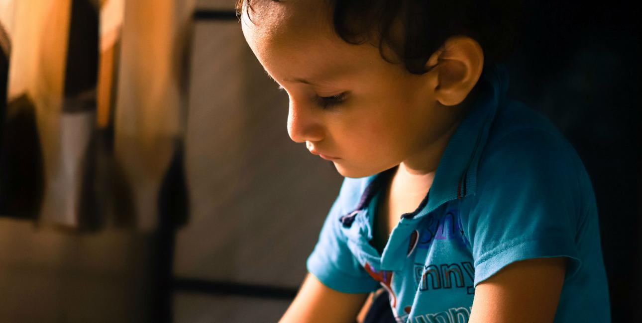 Dreng på gulv med papir. Foto: Yogesh Rahamatkar /Unsplash