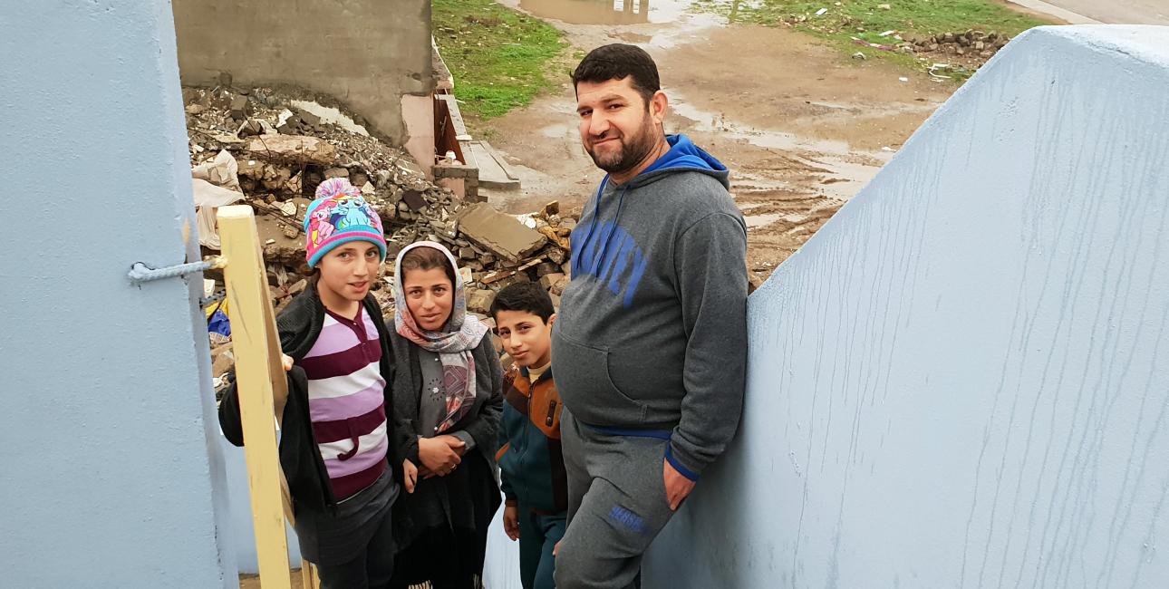 Lara , Ihsan og deres to børn foran deres ødelagte hus. Foto: Lina Musharbash og Andrea Rhodes